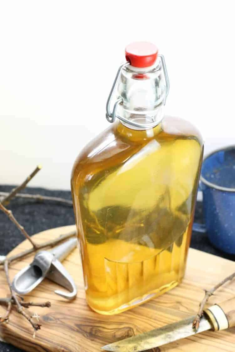 a glass bottle filled with light golden maple syrup