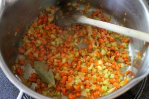 Small diced onions, carrot, and celery being cooked in a pot.