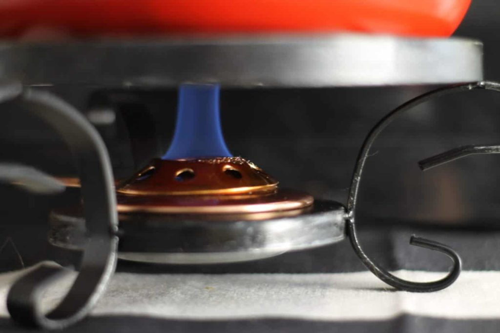 A blue flame burning underneath of a fondue pot