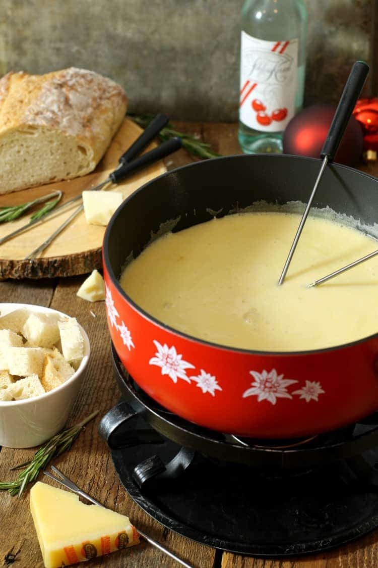 a large red fondue pot filled with swiss cheese fondue surrounded by crusty bread, kirsch, and cheese