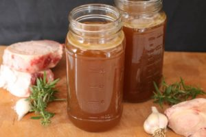 Two mason jars filled with homemade beef stock.