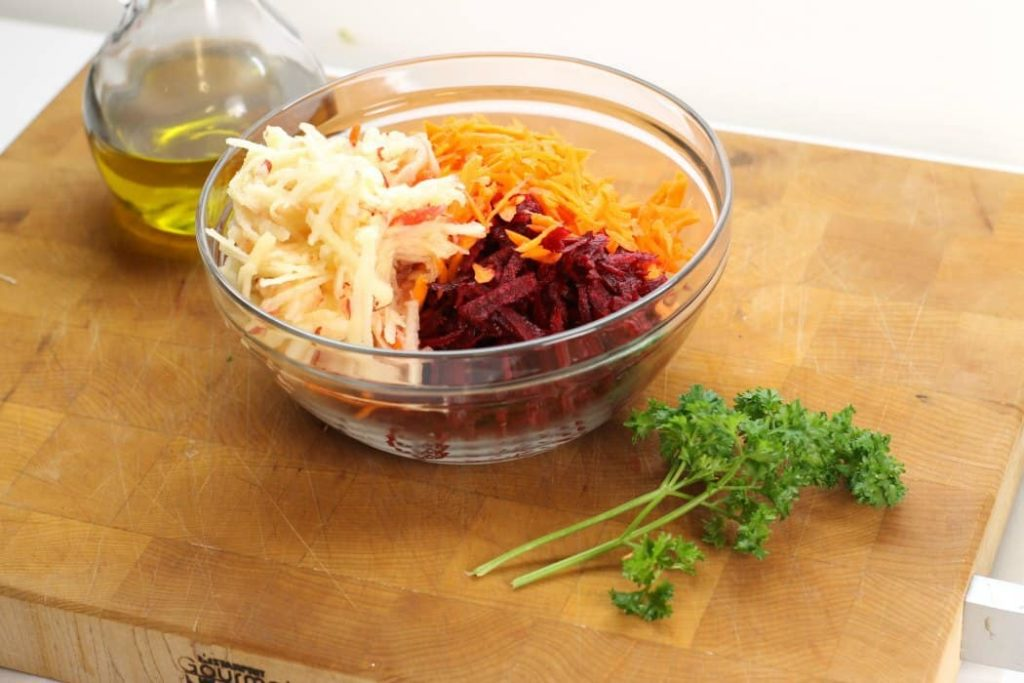 shredded beets, shredded carrots, and shredded apples in a bowl