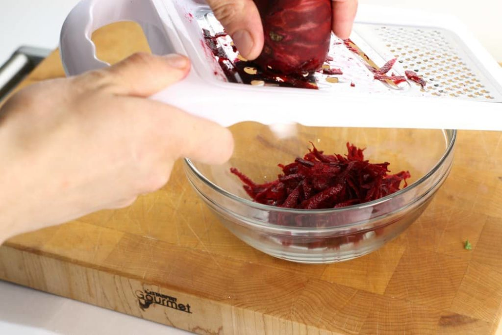 red beet being shredded on a handheld grater