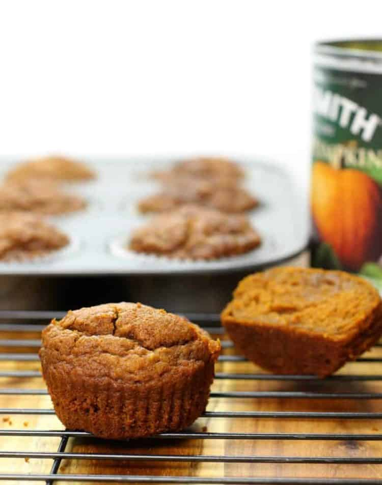 a cut in half pumpkin breakfast muffin on a black wire cooling rack