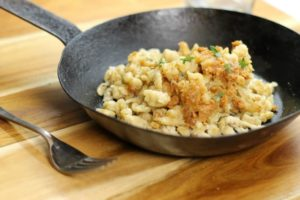 German kase spaetzle in a back steel pan on a wooden board