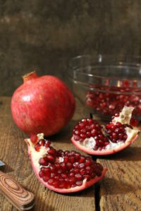 a freshly cut open pomegranate with no mess on a wooden table top