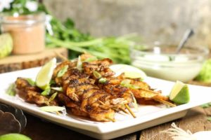 blackened shrimp skewers on a white platter surrounded by dip and various ingredients