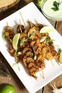 blackened shrimp skewers on a white platter garnished with lime wedges and green onion