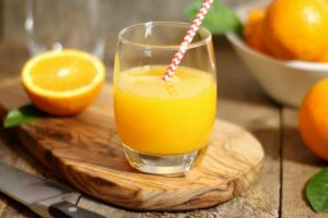 A glass of freshly squeezed orange juice on a wooden board