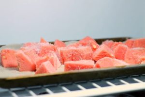 diced watermelon on a tray in the freezer