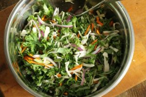 kale slaw mixed in a steel bowl without dressing