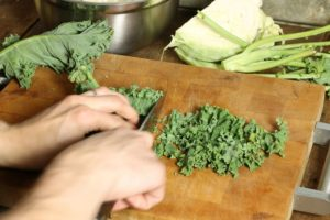 kale leaves being thinly shredded on a wooden cutting board