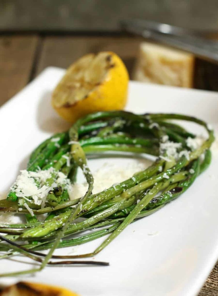 Grilled garlic scapes garnished with lemon and grated parmesan