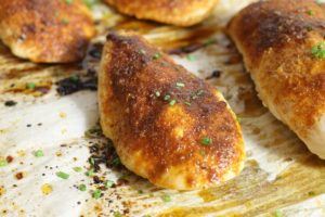 heavily seasoned oven baked chicken breasts on a sheet pan