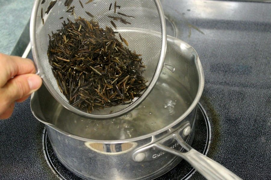adding wild rice to a boiling pot of water