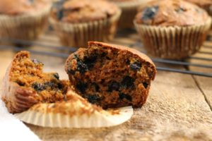 a blueberry bran muffin cut in half on a wooden board