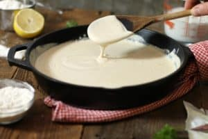 thickened bechamel sauce dripping of a wooden spoon into a cast iron pan