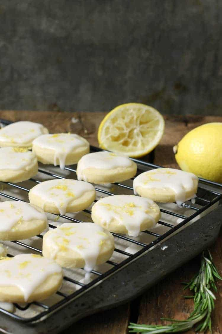 vertical image of glazed lemon shortbread cookies on a black cooling rack