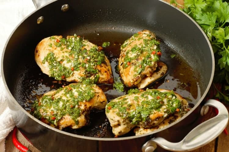 Pan seared chicken breasts topped with fresh chimichurri sauce in a pan