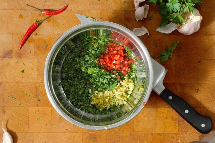ingredients for chimichurri in a steel bowl before mixing
