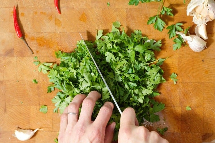 chopping a large amount of fresh parsley leaves