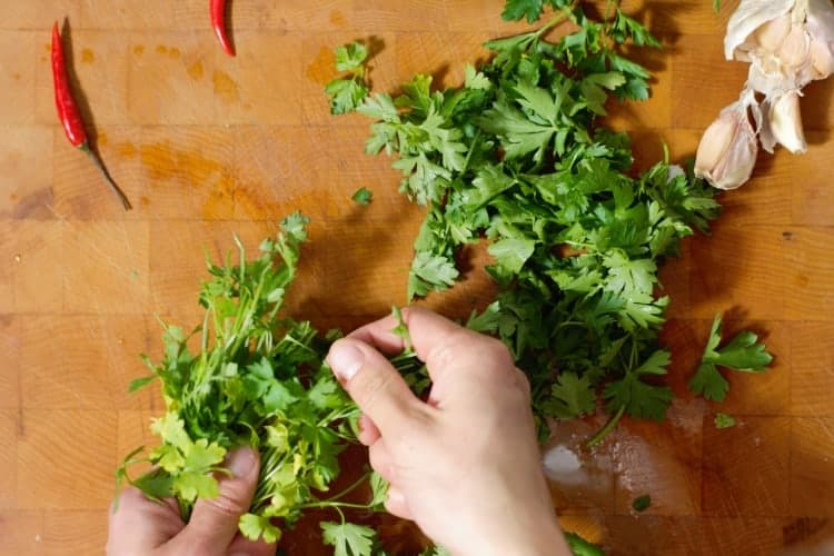 hands picking italian parsley leaves from stems over a wooden cutting board