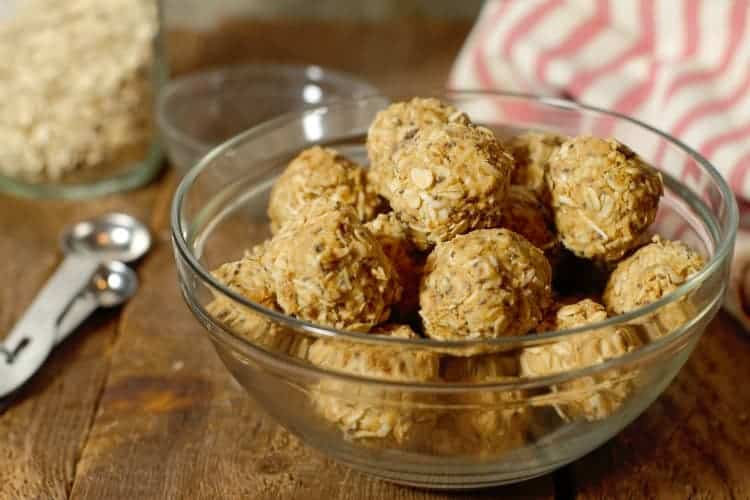 peanut butter protein balls in a glass bowl on a wood board tabletop