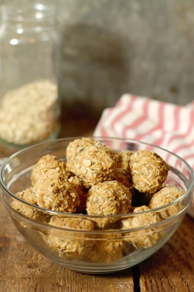 vertical image of peanut butter protein balls in a glass bowl on a wood board tabletop