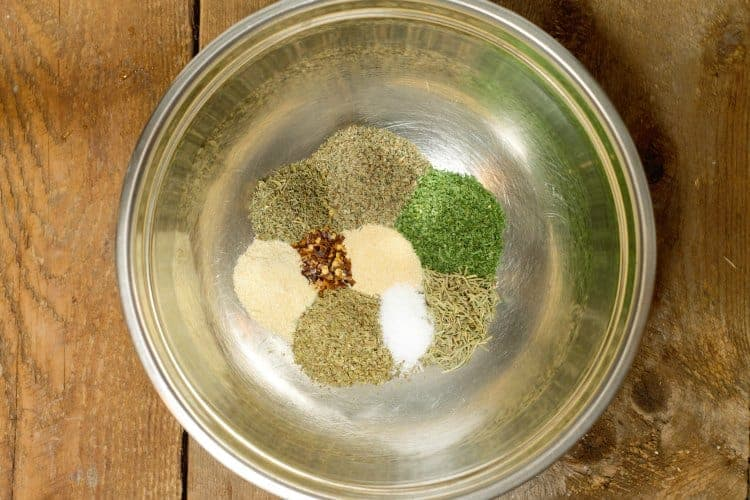 various herbs and spices used to make italian seasoning in a stainless steel bowl