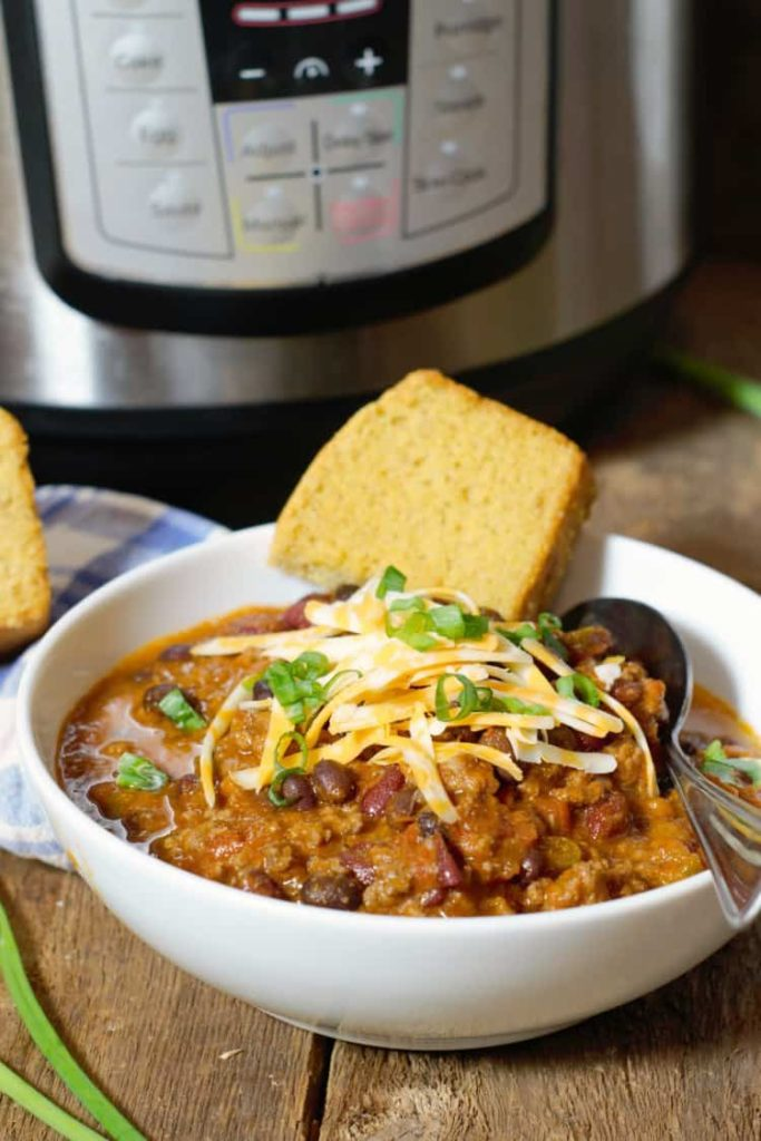 vertical image of instant pot chili served in a white bowl with cornbread