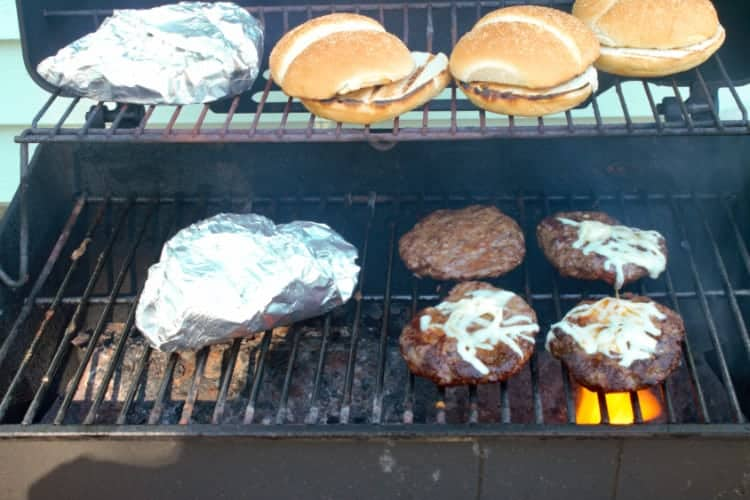 grilling tex mex burger patties, veggie foil pouch, and buns on the bbq