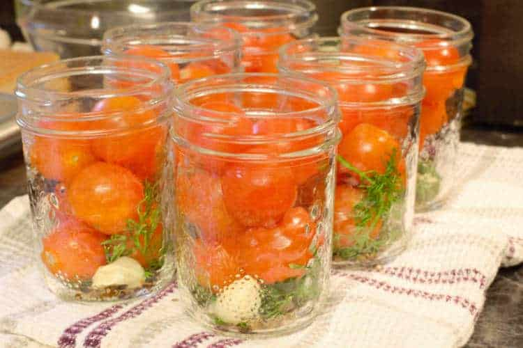 mason jars filled with spices and cherry tomatoes prior to pickling