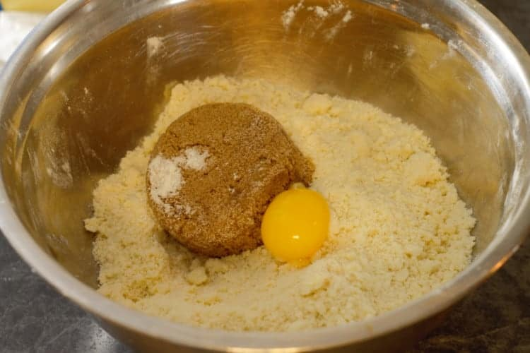 brown sugar and egg yolk being added to the flour and butter mixture
