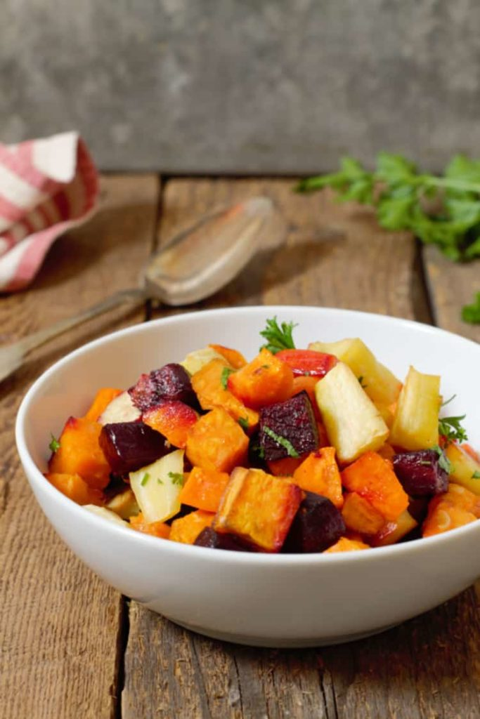 oven roasted root vegetables served in a white bowl on a rustic barn board background